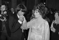 FILE - In this Dec. 16, 1977 file photo, designer Kenzo Takada kisses the hand of Italian actress Gina Lollobrigida after she awarded him as one of the ten most elegant men in the world in Rome, Italy. Fashion designer Kenzo Takada dies from COVID-19 complications at age 81 near Paris, spokeswoman and reports said Sunday Oct. 4, 2020. (AP Photo, file)