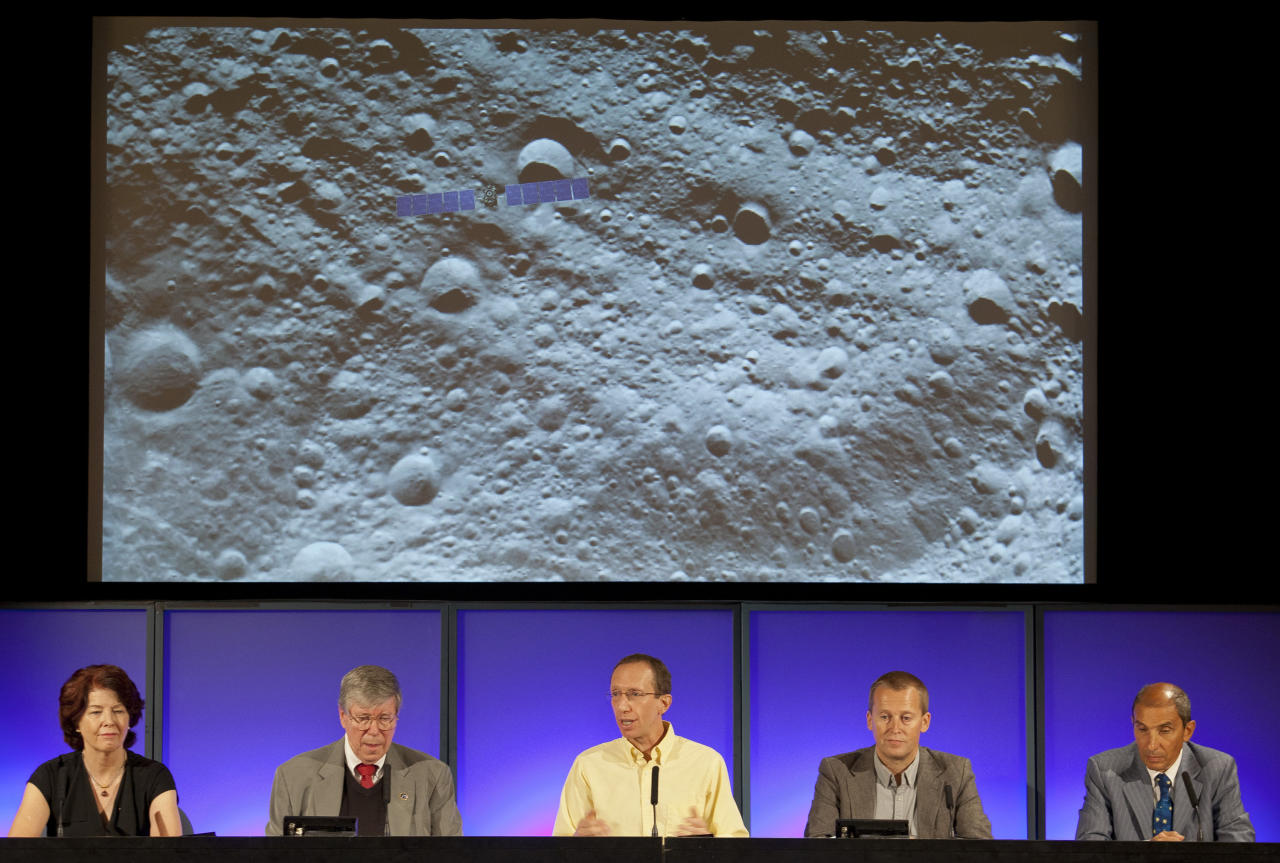NASA/Jet Propulsion Laboratory scientists unveil a detail image of the massive asteroid Vesta taken on July 24, by NASA's Dawn spacecraft, seen superimposed top left for scale, during a news conference at JPL in Pasadena, Calif., on Monday, Aug. 1, 2011. Scientist from left: Colleen Hartman, assistant associate administrator, Science Mission Directorate, NASA Washington. Christopher Russell, Dawn principal investigator, UCLA. Marc Rayman, Dawn chief engineer and mission manager, JPL. Holger Sierks, framing camera team, Max Planck Society, Katlenburg-Lindau, Germany. Enrico Flamini, chief scientist, Italian Space Agency (ASI), Rome, Italy. (AP Photo/Damian Dovarganes)