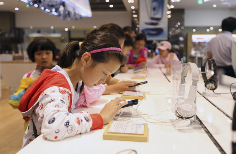 Chinese children try out Galaxy smartphones at Samsung's showroom in Seoul, South Korea, Friday, July 6, 2012. Samsung Electronics Co., the world's largest maker of memory chips, mobile phones, flat-screen panels and televisions, said Friday that its preliminary second-quarter operating profit jumped nearly 80 percent from a year ago to a record high. Analysts said the sharp rise was driven by Galaxy smartphone sales. (AP Photo/Hye Soo Nah)