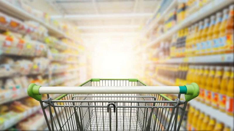 Supermarket aisle with empty green trolley
