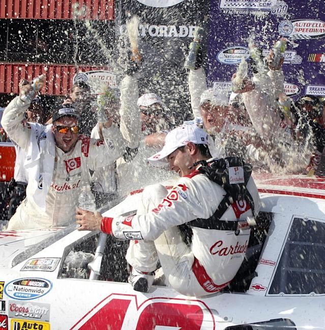 Kyle Larson, center, gets drenched by his team in Victory Circle after his win in the NASCAR Nationwide Series auto race in Fontana, Calif., Saturday, March 22, 2013(AP Photo/Alex Gallardo)