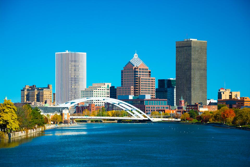 Downtown Rochester skyline with a bridge, and with the Genesee River in the foreground.