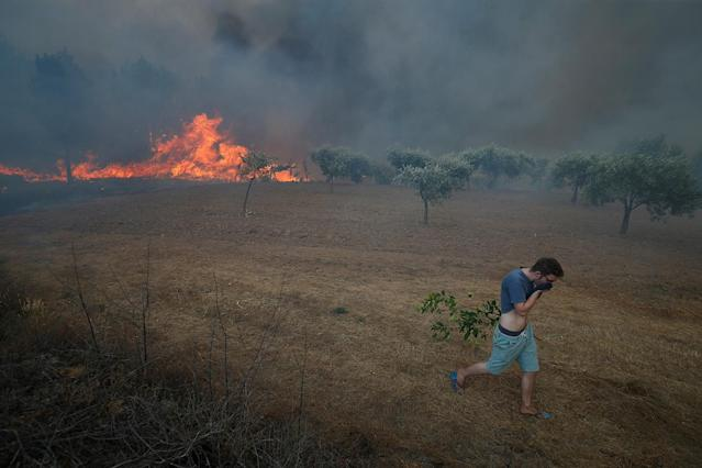 <p>A villager leaves a forest fire in the village of Brejo Grande, near Castelo Branco, Portugal, July 25, 2017. (Rafael Marchante/Reuters) </p>