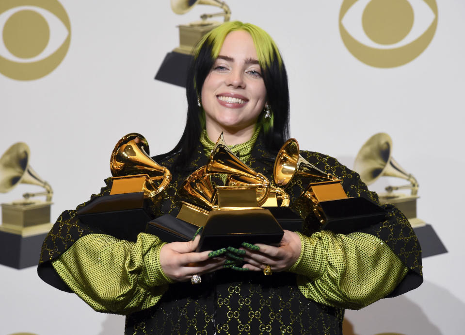 "Billie Eilish poses in the press room with the awards for best album and best pop vocal album for ""We All Fall Asleep, Where Do We Go?"", best song and record for ""Bad Guy"" and best new artist at the 62nd annual Grammy Awards at the Staples Center on Sunday, Jan. 26, 2020, in Los Angeles. (AP Photo/Chris Pizzello)"