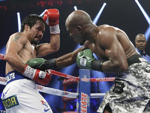 Timothy Bradley, right, connects with a right to the body of Manny Pacquiao, of the Philippines, in their WBO welterweight title boxing fight Saturday, April 12, 2014, in Las Vegas. Pacquiao won the bout by unanimous decision. (AP Photo/Isaac Brekken)