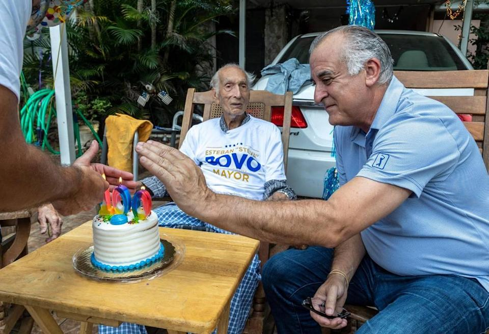 Hialeah mayoral candidate Esteban 'Steve' Bovo shields the candles on a cake for Reynaldo Flores, who recently turned 100 years old. Mr. Bovo stopped by Mr. Flores' house on Sept. 23, 2021, while he was out knocking on doors in the neighborhood.