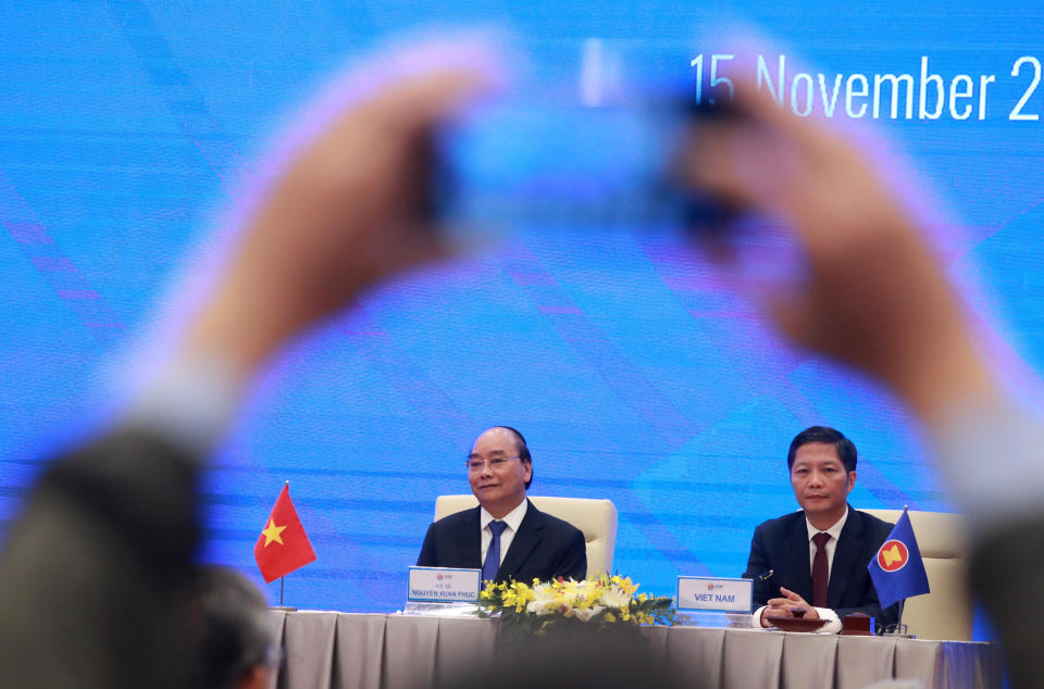 Vietnamese Prime Minister Nguyen Xuan Phuc, left, and Minister of Trade Tran Tuan Anh, right, attend a virtual signing ceremony of the Regional Comprehensive Economic Partnership, or RCEP, trade agreement in Hanoi, Vietnam on Sunday, Nov. 15, 2020. China and 14 other countries agreed Sunday to set up the world's largest trading bloc, encompassing nearly a third of all economic activity, in a deal many in Asia are hoping will help hasten a recovery from the shocks of the pandemic.(AP Photo/Hau Dinh)