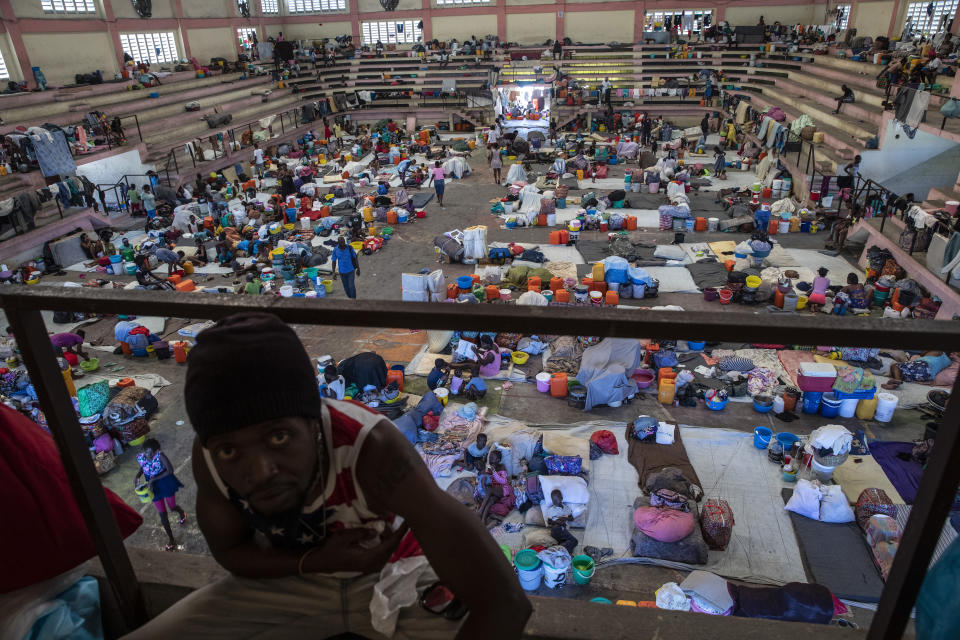 Internally displaced people due to gang violence shelter in the Center Sportif of Carrefour, in Port-au-Prince, Haiti, Saturday, Sept. 18, 2021. Families with young children have been sleeping on concrete floors of the gymnasium since mid-June, with only a sheet serving as a bed and their scant belongings stuffed into bags nearby. (AP Photo/Rodrigo Abd)