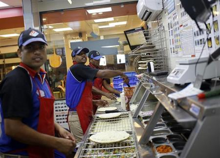 Workers prepare pizzas in the kitchen of a Domino's Pizza branch in New Delhi September 11, 2013. REUTERS/Anindito Mukherjee