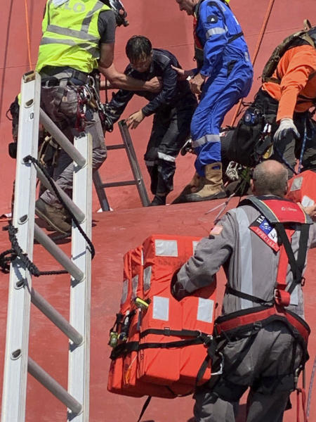 In this image released by the U.S. Coast Guard, a crew member of the cargo ship Golden Ray is helped off the capsized ship Monday, Sept. 9, 2019, off St. Simons Island, Ga. A fire broke out aboard the ship early Sunday, listing it to the side and blocking the shipping channel. The Coast Guard began pulling the four trapped crew members from the capsized ship, 20 others taken to land by by the coast guard. (U.S. Coast Guard via AP)