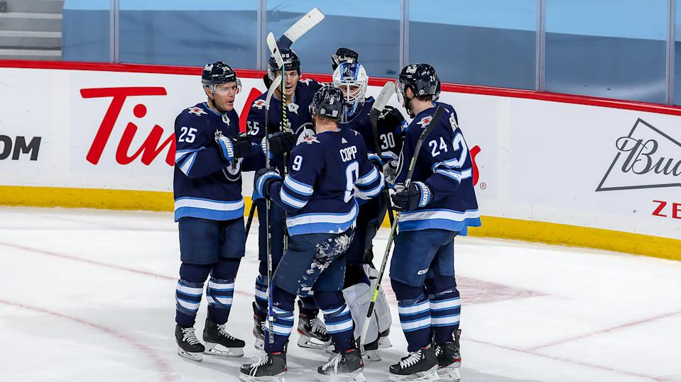 WINNIPEG, MB - FEBRUARY 2: Goaltender Laurent Brossoit #30 of the Winnipeg Jets is congratulated by teammates Paul Stastny #25, Mark Scheifele #55, Andrew Copp #9 and Derek Forbort #24 following a 3-2 victory over the Calgary Flames at the Bell MTS Place on February 2, 2021 in Winnipeg, Manitoba, Canada. (Photo by Jonathan Kozub/NHLI via Getty Images)