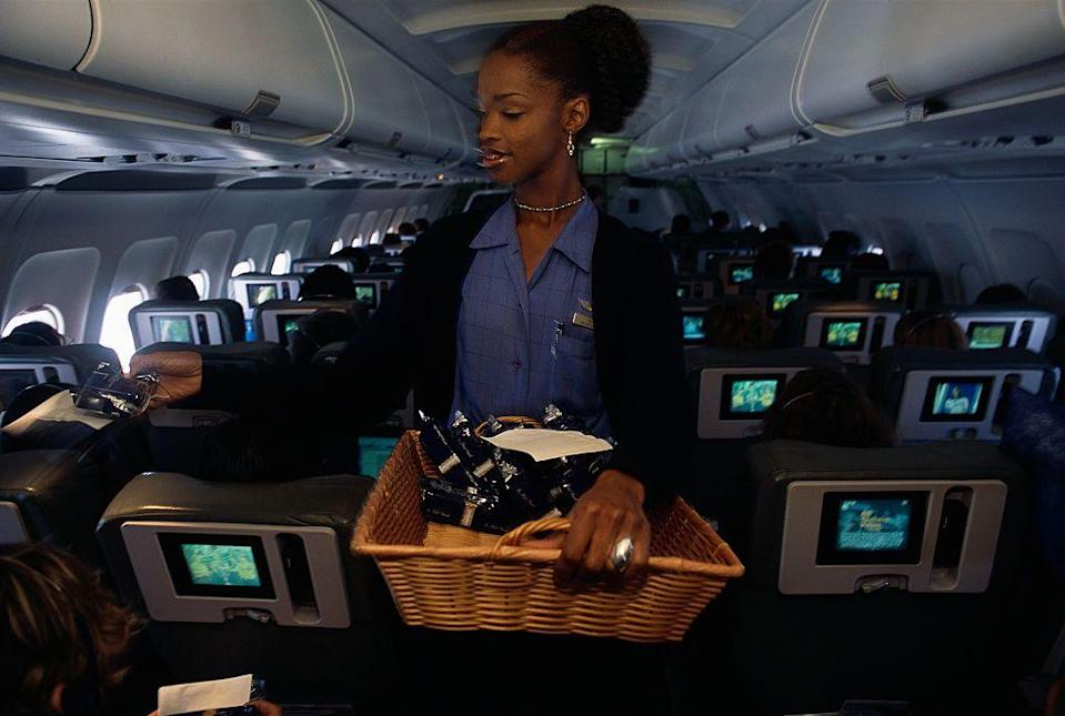 "<p>A flight attendant passing snacks to passengers on September 6, 2001. After 9/11, <a href=""https://www.npr.org/templates/story/story.php?storyId=5739457"" rel=""nofollow noopener"" target=""_blank"" data-ylk=""slk:flight attendant training"" class=""link rapid-noclick-resp"">flight attendant training</a> became much more expansive, with rigorous safety protocols and personal defense, according to NPR. </p>"