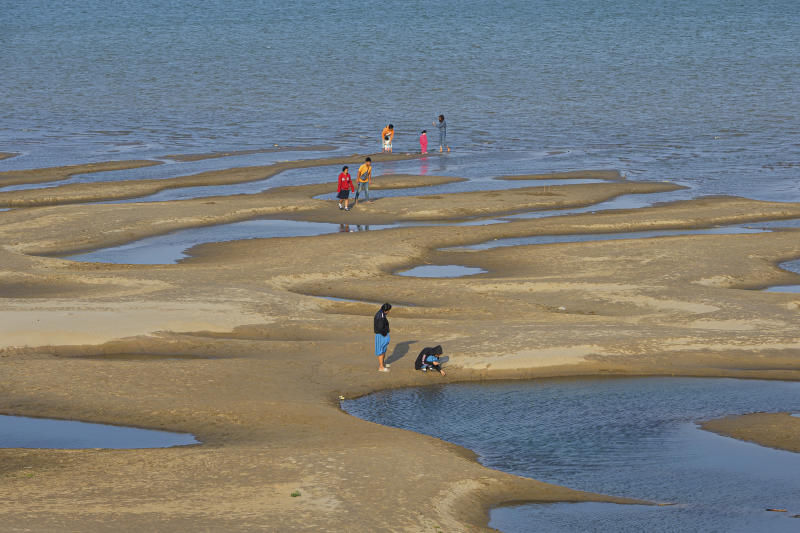 In this Wednesday, Dec. 4, 2019, photo, sightseers plays on a sandbar in the Mekong River in Nakhon Phanom province, northeastern Thailand. Experts say the aquamarine color the Mekong River has recently acquired may beguile tourists but it also indicates a problem caused by upstream dams. The water usually is a yellowish-brown shade due to the sediment it normally carries downstream. But lately it has been running clear, taking on a blue-green hue that is a reflection of the sky. The water levels have also become unusually low, exposing sandbanks in the middle of the river. (AP Photo/Chessadaporn Buasai)