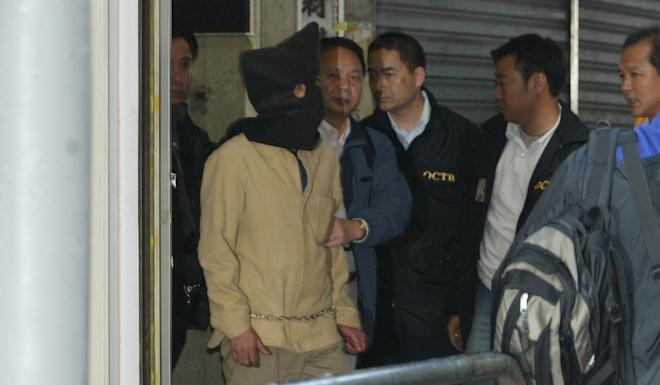 Police escort a hooded Kwai Ping-hung out of a building in Yau Ma Tei after his arrest in December 2003. Photo: Handout