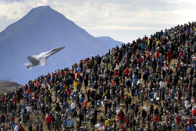 A crowd watches an F/A-18 Hornet fighter aircraft of the Swiss Air Force on October 11, 2012  doing a flight demonstration of the Swiss Air Force over Axalp in the Bernese Oberland.  AFP PHOTO / FABRICE COFFRINI