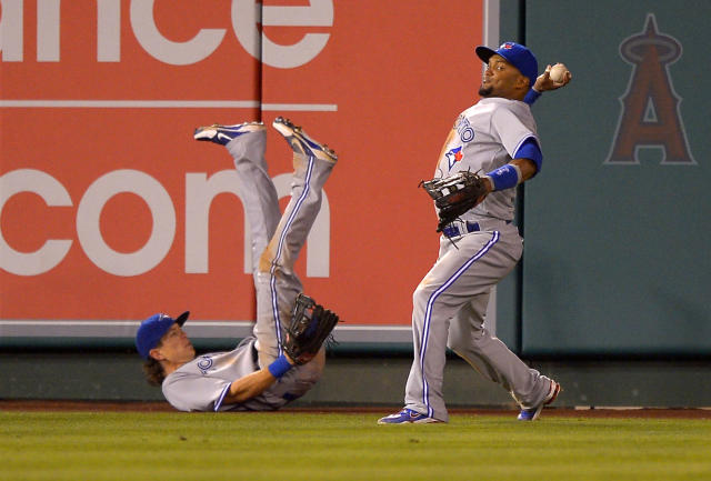 Toronto Blue Jays left fielder Emilio Bonifacio, right, throws in the ball as center fielder Colby Rasmus falls on a double by Los Angeles Angels' Chris Iannetta during the fourth inning of their baseball game, Friday, Aug. 2, 2013, in Anaheim, Calif. (AP Photo/Mark J. Terrill)