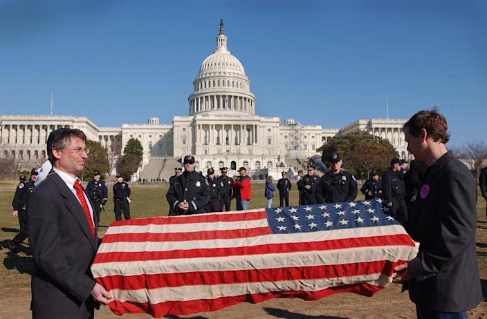 On March 9, 2003, Jim Schulman, left, and Michael Beer, both of Washington, D.C., hold a mock coffin draped with an American flag near the U.S. Capitol during a protest opposing a possible war with Iraq.