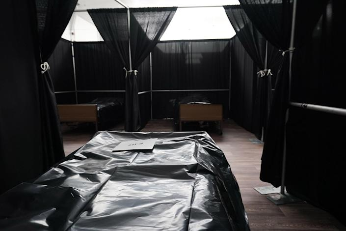 Image: Rows of beds separated by black fabric are set up as a temporary field hospital for COVID-19 patients is under construction at the USTA Billie Jean King national tennis center in the Borough of Queens (Bryan R. Smith / AFP - Getty Images)