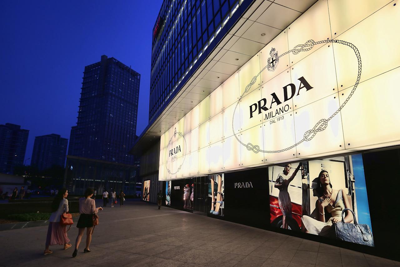 BEIJING, CHINA - JUNE 08:  Chinese women walk past the Prada store on June 8, 2012 in Beijing, China. According to the World Luxury Association 2011 annual official report , China is expected to replace Japan as the world's top consumer of luxury goods by 2012 with an expected luxury goods sales value of 14.6 billion U.S. dollars due to China's growing demand and declining consumption in Japan.  (Photo by Feng Li/Getty Images)
