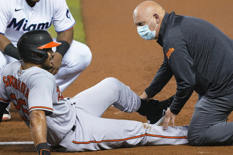 Baltimore Orioles' Anthony Santander (25) is assisted by a trainer after he was injured during the first inning of a baseball game against the Miami Marlins, Tuesday, April 20, 2021, in Miami. (AP Photo/Marta Lavandier)