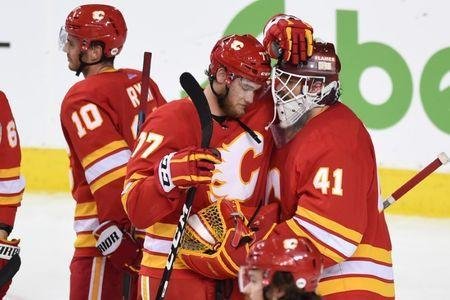 FILE PHOTO: Apr 19, 2019; Calgary, Alberta, CAN; Calgary Flames center Mark Jankowski (77) and goalie Mike Smith (41) react after their game against the Colorado Avalanche in game five of the first round of the 2019 Stanley Cup Playoffs at Scotiabank Saddledome. Avalanche won 5-1. Mandatory Credit: Candice Ward-USA TODAY Sports