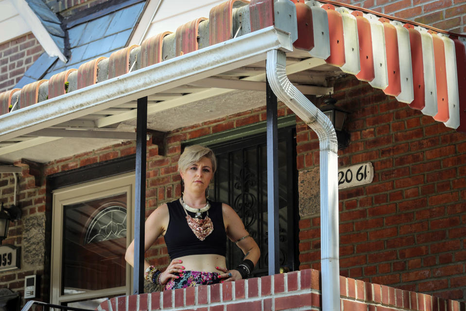Rachel Berry stands outside on her porch, Monday, July 6, 2020, in New York. Before the coronavirus pandemic, Berry worked as a bartender and waited tables, jobs that gave her enough time to work on her creative pursuits. But as New York City tries to reopen, there's concern that jobs for the city's creative class are no longer readily available. (AP Photo/Bebeto Matthews)