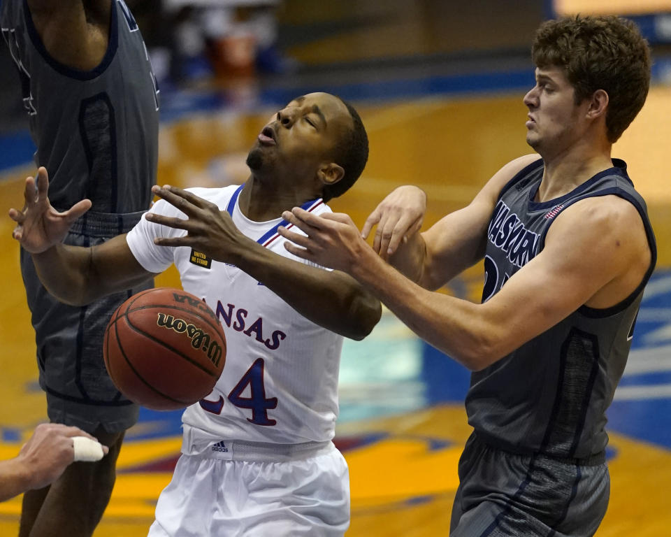 Kansas guard Bryce Thompson (24) is fouled by Washburn forward Will McKee, right, during the first half of an NCAA college basketball game in Lawrence, Kan., Thursday, Dec. 3, 2020. (AP Photo/Orlin Wagner)