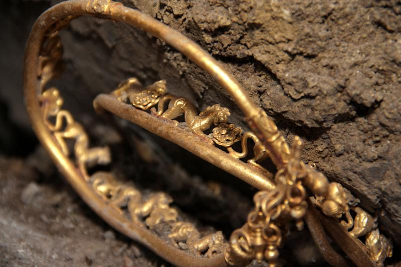 Archeologists show an artifact, part of 2,400-year old golden hoard found in an ancient Thracian tomb in northern Bulgarian village of Sveshtari, some 400 kilometer (250 miles) northeast of Sofia, on Thursday, Nov 8, 2012 Prof. Diana Gergova , archeologist and team leader said that among the artifacts, which date back to the end of the fourth or the beginning of the third century B.C., were gold jewelry and applications for horse trappings, a tiara with reliefs of lions and fantasy animals, as well as four bracelets and a ring. (AP Photo/ImpactPressGroup)