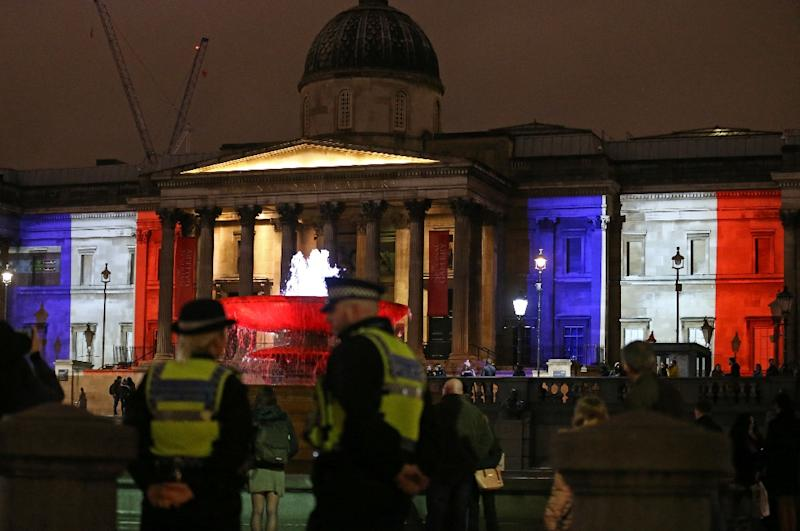 Police stand guard as London's National Gallery and the fountains in Trafalgar Square are lit up in the colours of the French national flag in solidarity with France following the Paris attacks (AFP Photo/Justin Tallis)