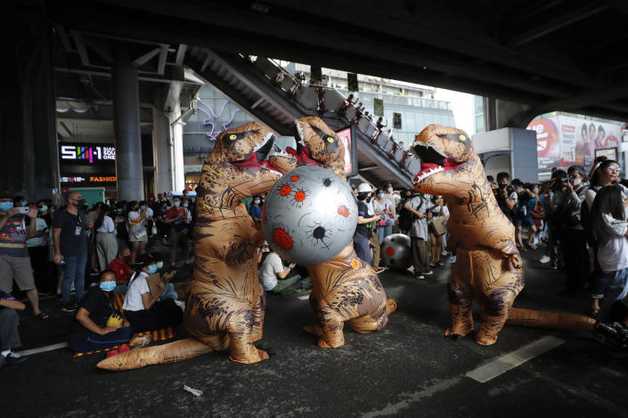 """Dinosaur mascots hold a large ball depicting an asteroid during a student rally in Bangkok, Saturday, Nov. 21, 2020. Organized by a group that mockingly calls themselves """"Bad Students,"""" the rally calls for educational reforms and also supports the broader pro-democracy movement's demands for constitutional change. (AP Photo/Sakchai Lalit)"""