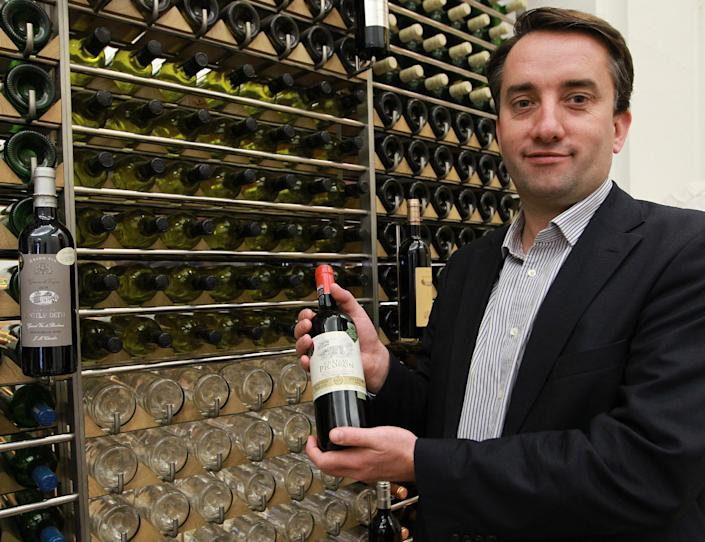 In this photo dated Wednesday, Nov. 13, 2013, Christophe chateau, head of the communication of the Bordeaux winegrower's professional association displays a bottle of wine at his office in Bordeaux, southwestern France. Counterfeiting has dogged wine as long as it has been produced, but it is getting more sophisticated and more ambitious, particularly as bottle prices rise due to huge demand in new markets, mainly in Asia. (AP Photo/Bob Edme)