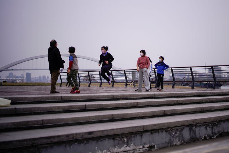 People wearing face masks jump rope at a park, as the country is hit by an outbreak of the novel coronavirus, in Shanghai