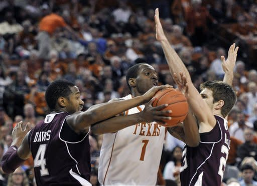 Texas guard Sheldon McClellan works between Texas A&M center Keith Davis, left, and guard Zach Kinsley during the first half of an NCAA college basketball game Wednesday, Jan. 11, 2012, in Austin, Texas. (AP Photo/Michael Thomas)