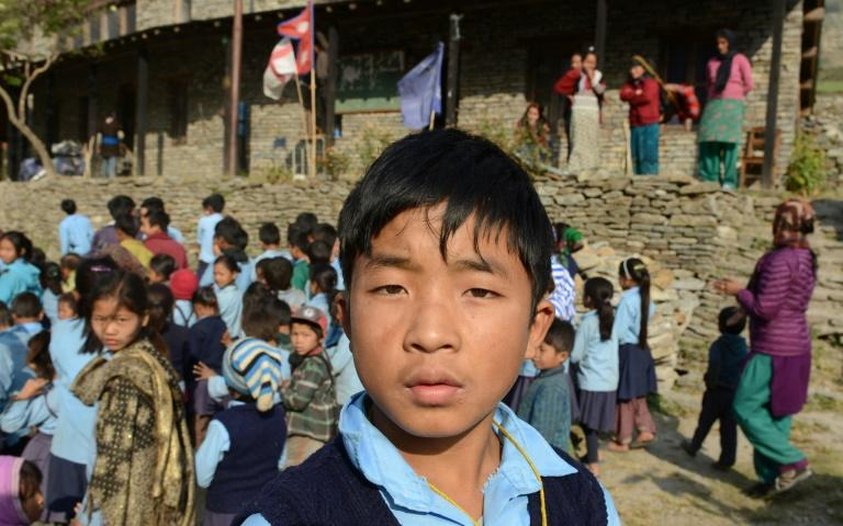 Nepalese school student Dawa Phunchok Lama poses in front of the Shree Buddha Secondary School in the village of Sirdibas in Gorkha District