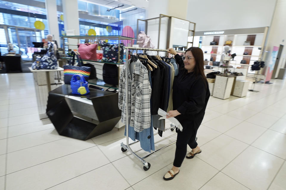 A Nordstrom employee moves a rack of merchandise at the Nordstrom NYC Flagship store, in New York, Wednesday, July 14, 2021. Like many of its peers, venerable department store chain Nordstrom is having a tough time keeping pace with customer demand for new clothes because of supply issues. (AP Photo/Richard Drew)