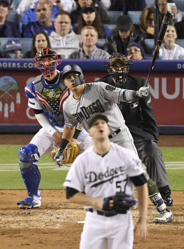 San Diego Padres' Christian Villanueva watches his two-run home run off Los Angeles Dodgers starting pitcher Alex Wood, front, during the sixth inning of a baseball game Saturday, May 26, 2018, in Los Angeles. (AP Photo/Mark J. Terrill)