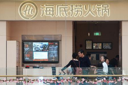 People wait outside Haidilao, a Chinese hotpot chain restaurant, as a screen shows the waiting numbers on the wall, in Zhengzhou, Henan province, China September 24, 2018. REUTERS/Stringer