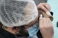 While waiting on a delivery at Hanan Products, Rabbi Mendel Einhorn catches up on some work from another job by looking for insects in samples of their products, Thursday, Jan. 7, 2021, in Hicksville, N.Y. (AP Photo/Seth Wenig)