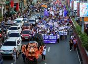 An effigy of Philippine President Rodrigo Duterte is seen while women's rights activists march along a busy street during a celebration of the International Women's Day in Quiapo city, Metro Manila
