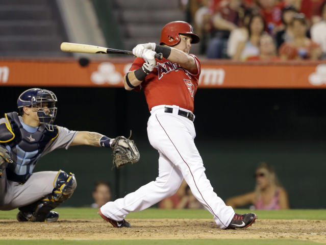 Los Angeles Angels' Kole Calhoun singles in a run against the Tampa Bay Rays catcher Jose Lobaton at left, in the third inning of a baseball game in Anaheim, Calif., Monday, Sept. 2, 2013. (AP Photo/Reed Saxon)
