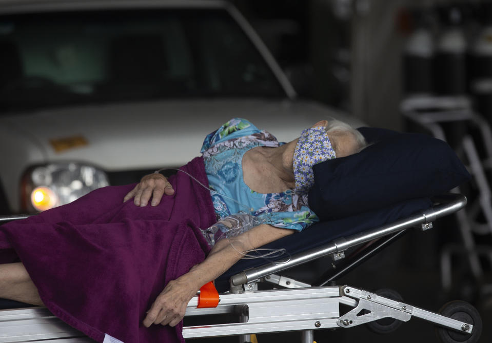 A patient arrives at the Steve Biko Academic Hospital's outside parking area in Pretoria, South Africa, Monday, Jan. 11, 2021. As the numbers of new confirmed cases rise, South Africa's hospitals are exceeding capacity, according to health officials. (AP Photo/Denis Farrell)