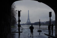 A man jogs near the flooded Seine river banks in Paris, Sunday, Feb. 7, 2021. In the Paris region, the Seine River overflowed its embankments for a fifth day. (AP Photo/Christophe Ena)