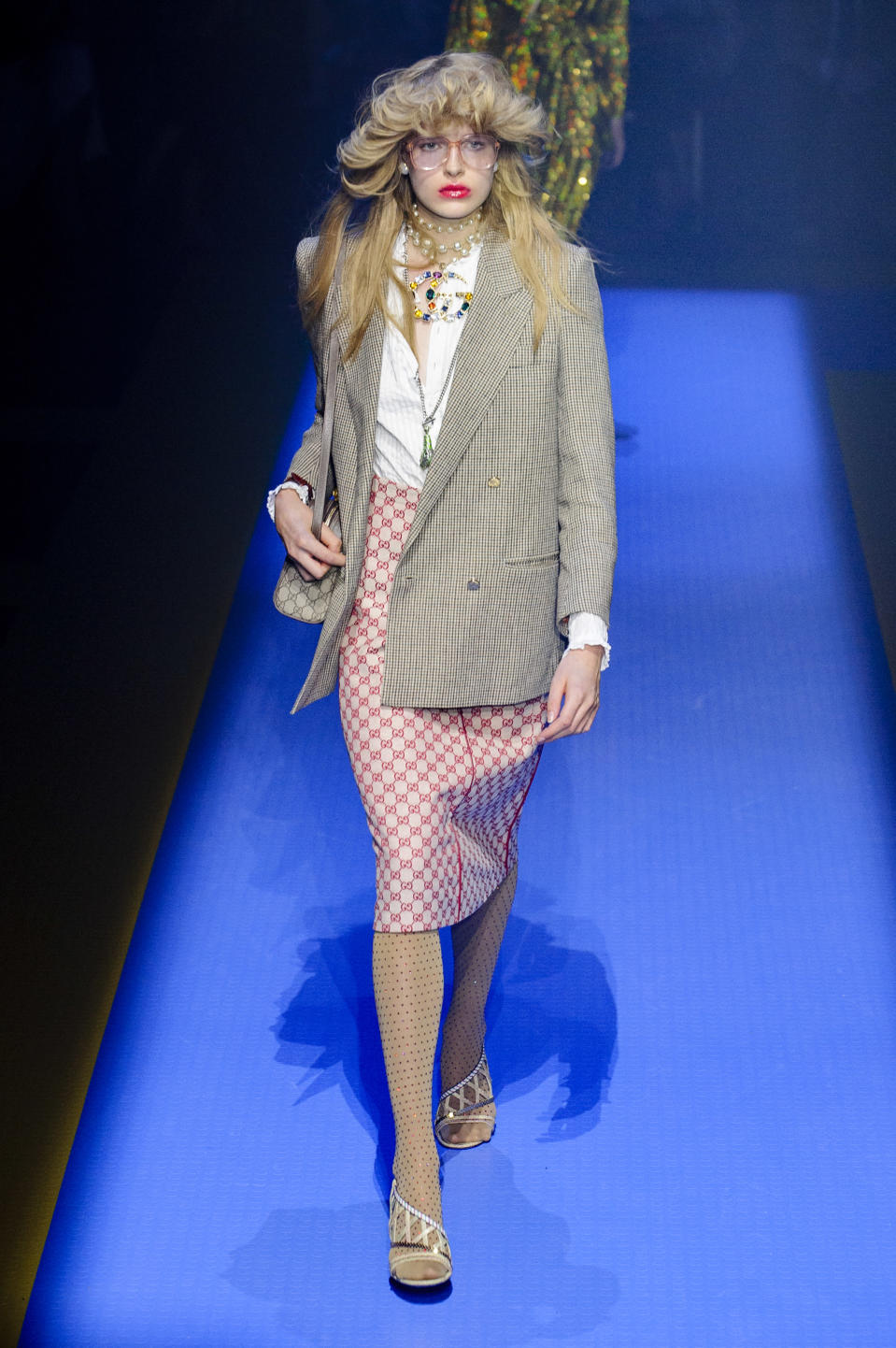 <p><i>Model wears a plaid blazer and red Gucci logo skirt, with a white shirt and layered bright jewelry. (Photo: ImaxTree) </i></p>
