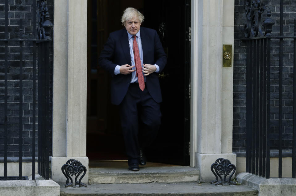 """Britain's Prime Minister Boris Johnson comes out to applaud on the doorstep of 10 Downing Street, during the weekly """"Clap for our Carers"""", in London, Thursday, May 28, 2020. The COVID-19 coronavirus pandemic has prompted a public display of appreciation for care workers. The applause takes place across Britain every Thursday at 8pm local time to show appreciation for healthcare workers, emergency services, armed services, delivery drivers, shop workers, teachers, waste collectors, manufacturers, postal workers, cleaners, vets, engineers and all those helping people with coronavirus and keeping the country functioning while most people stay at home in the lockdown. (AP Photo/Kirsty Wigglesworth)"""