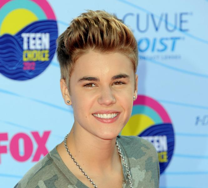 FILE - This July 22, 2012 file photo shows singer Justin Bieber arriving at the Teen Choice Awards in Universal City, Calif. Los Angeles prosecutors have filed criminal charges against a paparazzo photographer for allegedly racing across a Los Angeles freeway in an effort to get photographs of Justin Bieber. The case marks the first use of a 2010 state law designed to prevent paparazzi from dangerously pursuing celebrities for photos. The City Attorney's office said Wednesday that 30-year-old Paul Raef faces four charges, including reckless driving with the intent to capture pictures for commercial gain, following another vehicle too closely, and reckless driving. (Photo by Jordan Strauss/Invision/AP, file)