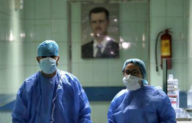 Medical workers walk in a hospital ward in the Syrian capital Damascus, with a picture of President Bashar Assad behind them, March 19, 2020, as the facility prepared to quarantine COVID-19 patients. / Credit: LOUAI BESHARA/AFP/Getty