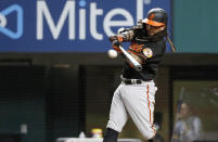 Baltimore Orioles' Freddy Galvis hits a double during the fifth inning of the team's baseball game against the Texas Rangers in Arlington, Texas, Friday, April 16, 2021. (AP Photo/Roger Steinman)