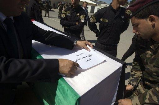 Palestinian security forces place the name of Anan Mohammed Hanani of Nablus on his flag-draped coffin during preparations for the funeral procession of 91 Palestinians whose remains were returned by Israel on Thursday