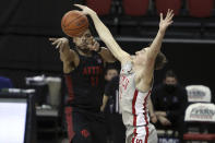 San Diego State's Matt Mitchell (11) passes the ball against UNLV's Moses Wood (1) during the second half of an NCAA college basketball game Wednesday, March 3, 2021, in Las Vegas. (AP Photo/Joe Buglewicz)