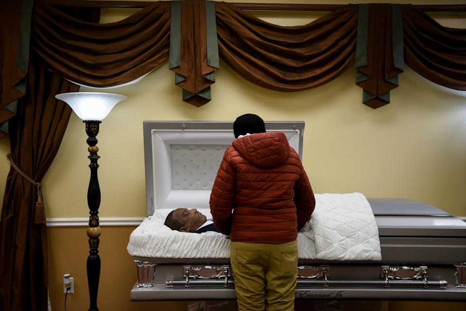 Samantha Emanuel reacts while viewing the body of her father, Samuel Emanuel Jr., 55, who died from complications from the coronavirus disease (COVID-19), during a private viewing held for the family at Pryority Funeral Experience, in Houston, Texas, U.S., February 11, 2021.  REUTERS/Callaghan O'Hare     SEARCH